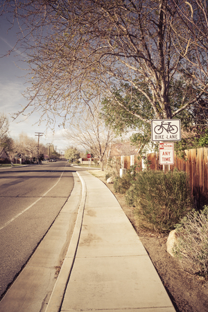 subdivision: Bike Lane sign in a typical U.S. middle class neighborhood subdivision with a sidewalk. Stock Photo