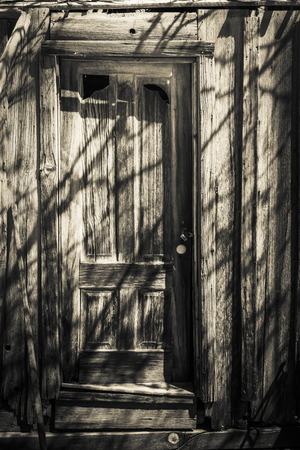 ghost town: Old door in an abandoned ghost town with tree shadows in black and white.