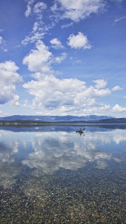yukon territory: Person kayaking through cloud reflections on calm water in Atlin Lake, Yukon Territory in summer.