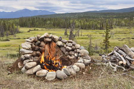 Campfire in a rock ring overlooking a valley view in the Yukon Territory of Canada in summer. Stock Photo