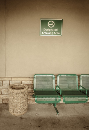 Designated area for smoking with sign and trash can outdoors at an airport. Stock Photo - 64522260