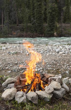 Campfire burning in rock ring beside the Wheaton river in Yukon Territory Canada in summer.