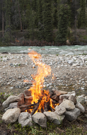 Campfire burning in rock ring beside the Wheaton river in Yukon Territory Canada in summer.