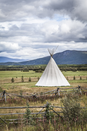 first nations: Tipi in rural Canada with storm clouds and rustic wooden fencing.