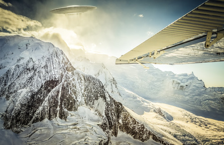photomanipulation: UFO seen from the window of a small plane in Alaskan mountains. Stock Photo