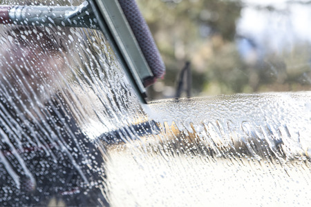 Action shot of a car windshield being cleaned with a squeegee.