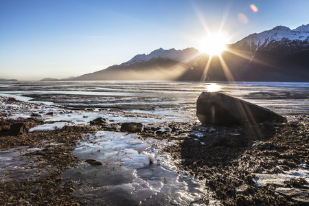 Sunset on the Chilkat River estuary beaches near Haines Alaska with ice in early winter.