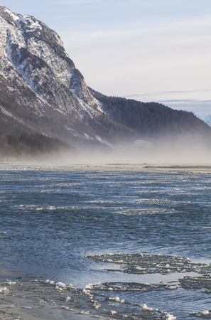 Ice forming on the Chilkat river in Southeast Alaska near Haines with fog rising.