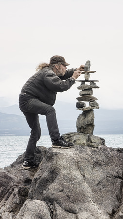 Man carefully stacking rocks in a cairn by the sea.