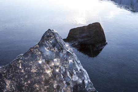 Large chunk of translucent sea ice on a beach in Southeast Alaska at sunset with an incoming tide. Stock Photo