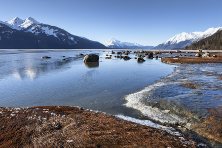 Chilkat Estuary near Haines Alaska in winter with melting ice on a sunny day. Stock Photo