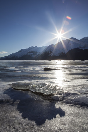 Sunburst at sunset on the Chilkat river near the estuary in winter with shadows from a large translucent ice chunk.