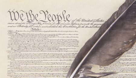 Close crop of the preamble to the United States Constitution with an eagle feather pen.