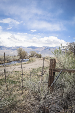 Fence to keep cattle in near Bishop, California with a water canal and dirt road i the backgrounds.