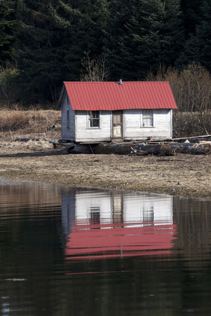 Small rustic house on a beach in Southeast Alaska reflected in calm water.
