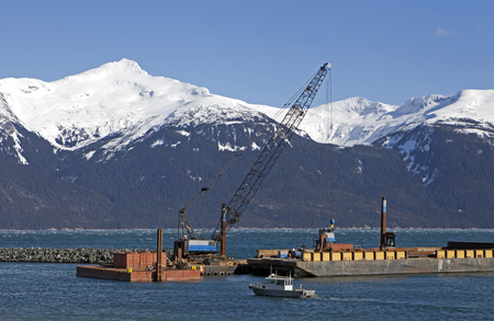 Large dredging rig with crane near the harbor breakwater in Haines Alaska with small boat going by.