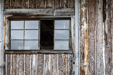 Rustic log sided cabin in the Yukon in Canada abandoned with a missing window panes. Stock Photo
