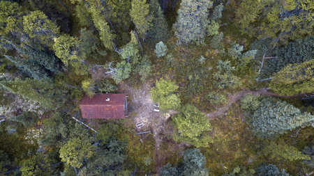 Aerial drone photo of a rustic Yukon Canadian cabin in the forest.