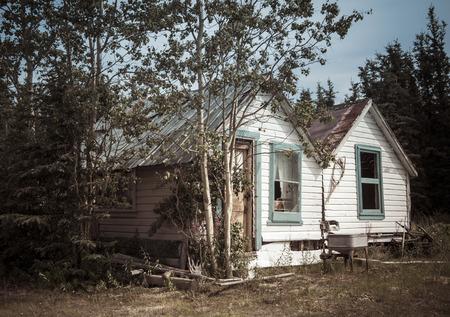 여름에 유콘 캐나다에서 오래 된 소박한 목조 주택 빈티지 모습에 대 한 처리.