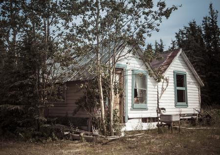 Old rustic wooden house in the Yukon Canada in summer processed for a vintage look. Archivio Fotografico