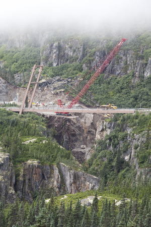 Highway repairs on a very steep section of White Pass in Southeast Alaska with a crane and trucks in summer with fog.