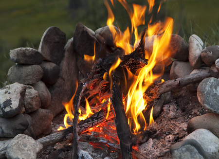 Close up shot of a burning campfire with a stone fire circle in summer. Stock Photo