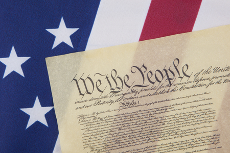 Close up of the U.S. Constitution document with We the People on an American flag.