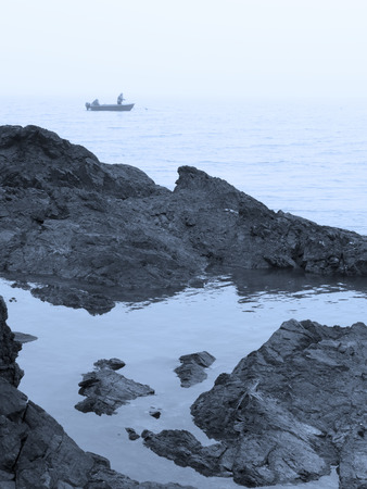 Small boat with people fishing in the fog near a rocky shore.