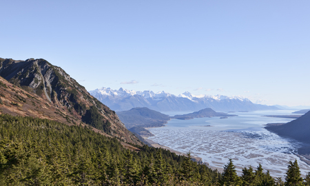 Reward for a steep hike up the Seven Mile Saddle trail near Haines in Southeast Alaska is a view of the Chilkat River and Inlet with mountains.