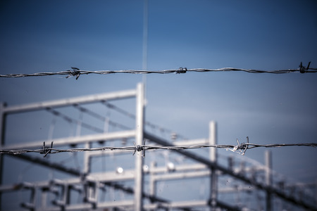 Behind a barbed wire security fence with the focus on the fence, with a power plant beyond out of focus with blue sky.