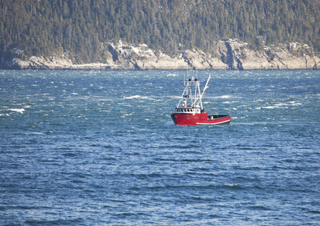 Red fishing boat moving through waves in the Lynn Canal of Southeast Alaska on a sunny day. Stock Photo