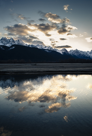 Sunset over the Chilkat mountains in Southeast Alaska near Haines with snow on the peaks and cloud reflections in the Chilkat river.