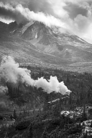 Steam locomotive train heading up in the mountains of Canada to White Pass on a cloudy day.