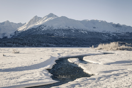 Klehini river in early winter after the first snow with the Chilkat mountains in the background. Stock Photo