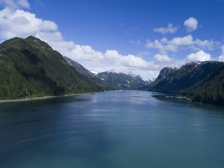 View of Dundas Bay in Glacier National Park on a calm summer day with puffy clouds.