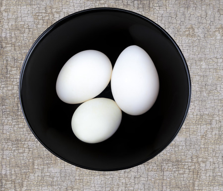 Three large white duck eggs in a black bowl on a textured surface shot from ablove. Stock Photo