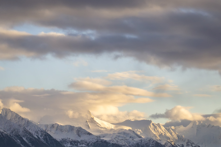 Snow capped Coast Range mountains in Southeast Alaska with sunset clouds. Stock Photo