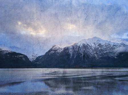 Southeast Alaskan mountains at sunset at low tide with textures added. Stock Photo