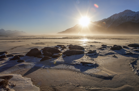 Winter sunburst sunset on the Chilkat river estuary at low tide near Haines Alaska with wind blowing silt on a clear day. Stock Photo