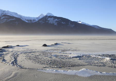 Chilkat river inlet near Haines Alaska in winter frozen and covered with blowing silt on a windy winter day. Stock Photo