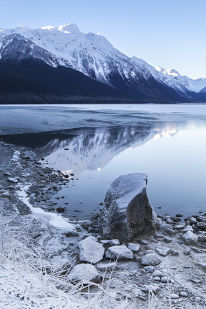 Chilkat lake with ice forming on open water with mountains in the background reflected on a clear winter day.