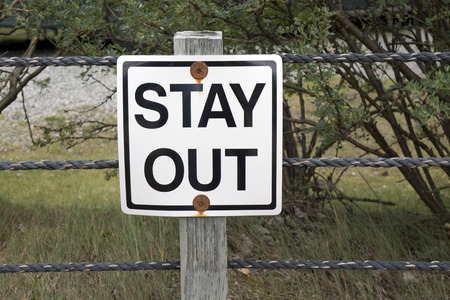 Rustic Stay Out sign on a rope fence in summer.