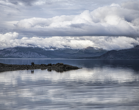Storm clouds over Kluane lake in summer with a couple standing on a rocky outcropping. Stock Photo