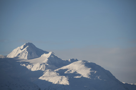 Close up of the snow covered Chilkat Mountains in Southeast Alaska with a blue sky.