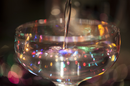 Liquid being poured into a cocktail glass blurred with party lights in the background and reflected.