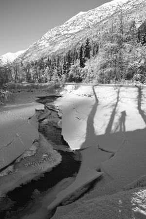 Cracked ice beside a creek in winter with shadows of trees and a person in the snow in black and white.