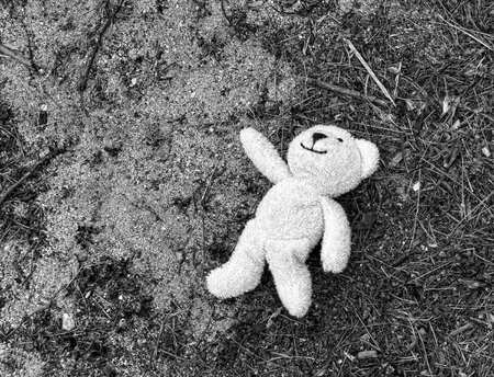 Small cloth toy stuffed bear left behind in the sand in black and white.