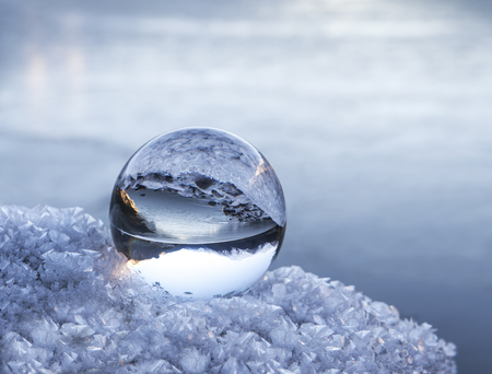 Alaskan mountains and lake reflected in a glass ball on a frosty rock in winter.