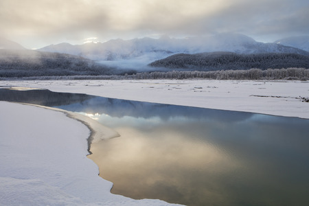 Fog decending on the Chilkat river at sunset with reflections on open water in winter. Stock Photo