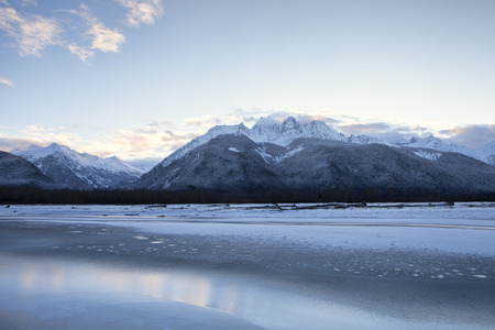 Pink clouds after sunset on the iced up Chilkat River in winter near Haines Alaska. Stock Photo